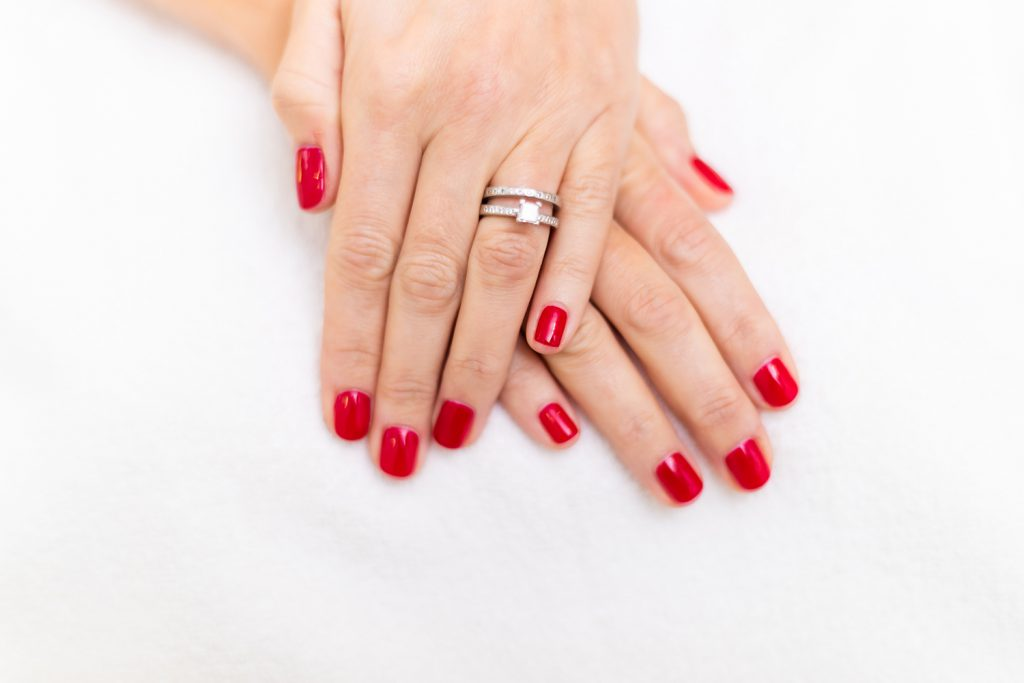 Woman's hands with red polish on her fingernails