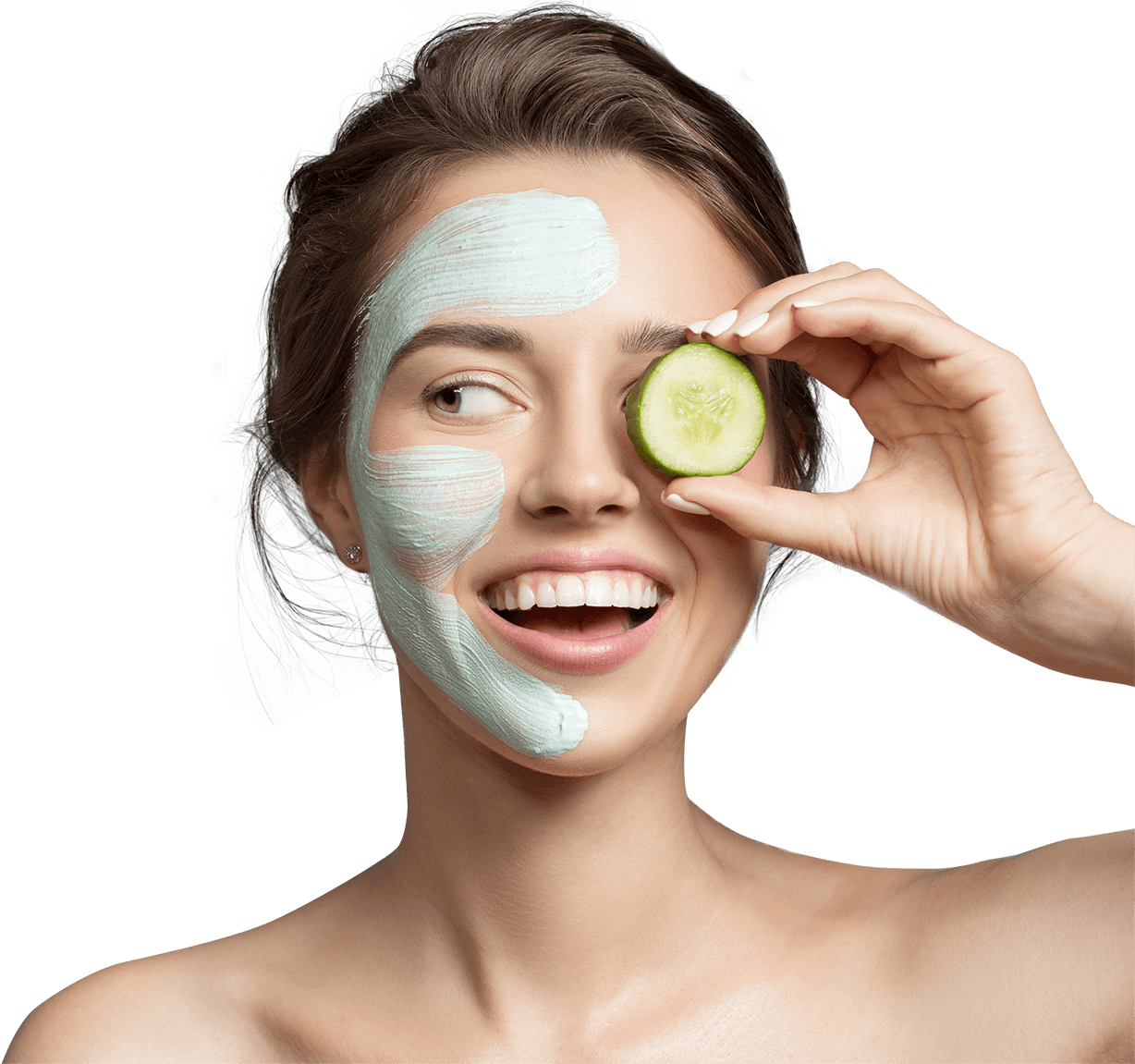 Woman wearing face cream holding a cucumber slide in front of her left eye