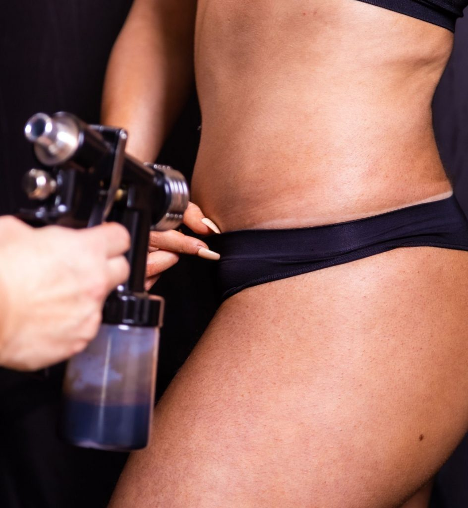 Woman being sprayed with fake tan